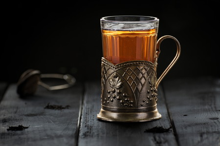 tea filter: Traditional Russian tea served in glass with vintage brass glass holder podstakannik