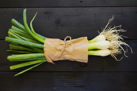 washed out: Raw food ingredients bouqet of spring onions on black boards. Top down. Flat lay. Stock Photo
