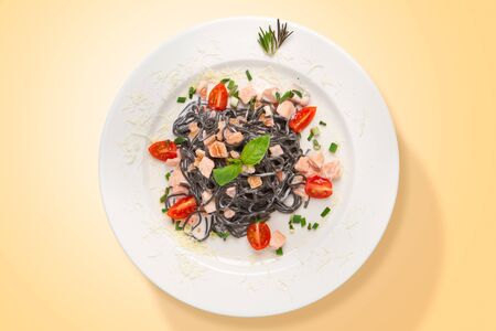 Italian squid ink pasta with salmon and parmesan cheese served in a white plate. Top view. Food from above