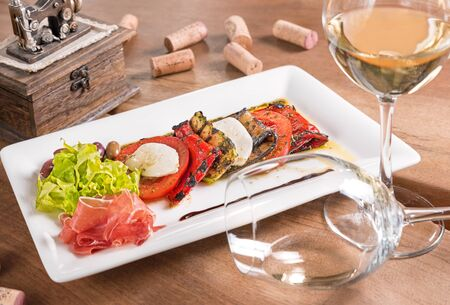 Antipasti with white wine,stewed vegetables and mozzarella served in a white plate.