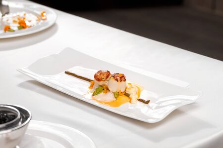 Coquilles Saint – Jacques, green asparagus and mushrooms - scallops, white mushroom cream, mushroom tortellini, green asparagus, bisque sauce and veloute, served in a white plate on a restaurant table. Stockfoto