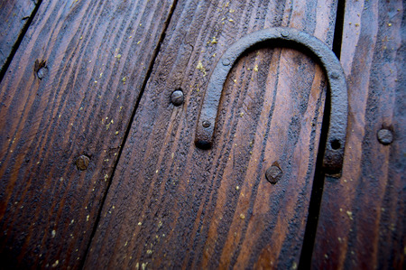 smithery: Old rusty horseshoe pinned to a wall of brown wooden boards Stock Photo