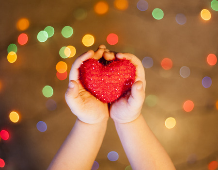 baby in hands: baby hands holding a heart on lights background