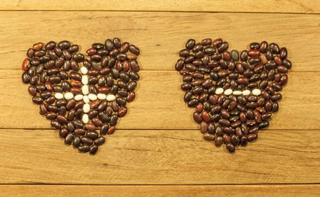 opposites: two hearts plus and minus the beans (attraction of opposites) Stock Photo