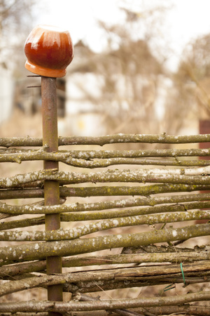 clay pot: old fence with a clay pot