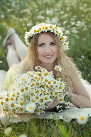 Beautiful lady on camomile field full of flowers