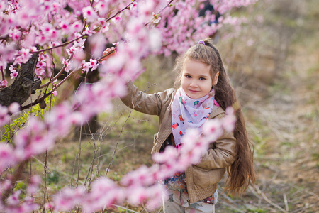 Cute beautiful stylish dressed blond girl standing on a field of spring young peach tree with pink flowers.smiling girl dressed in in pink in spring season