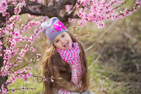 Cute beautiful stylish dressed girl standing on a field of spring young peach tree with pink flowers. Stock Photo
