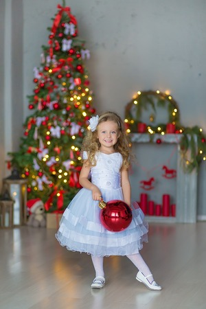 sexy girl dance: Young beautiful girl in blue white elegant evening dress near christmas tree and presents on a new year eve