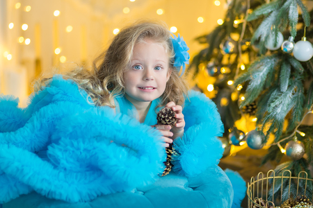 Young beautiful girl in blue white elegant evening dress sitting on floor near christmas tree and presents on a new year eve Interior with christmas decorations. Shallow DOF and bokeh background