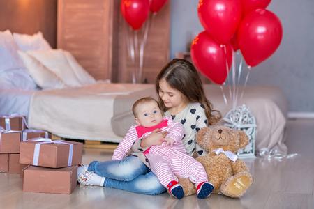 귀여운 소녀와 아기 빨간색 풍선에 함께 생일을 축 하합니다.