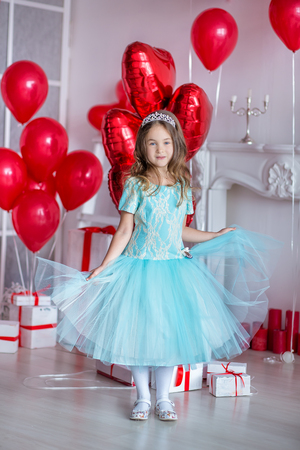 Cute girl celebrating birth day together close to red balloons.