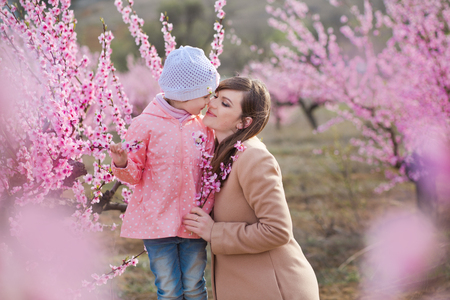 Cute beautiful stylish dressed brunette girl with mother mom standing on a field of spring young peach tree with pink flowers.Lady dressed in rain clothes and blue hat rubber boots spring season