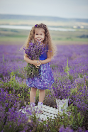 Pretty young girl sitting in lavender field in nice hat boater with purple flower on it Stock Photo