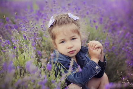 boater: Pretty young girl sitting in lavender field in nice hat boater with purple flower on it Stock Photo
