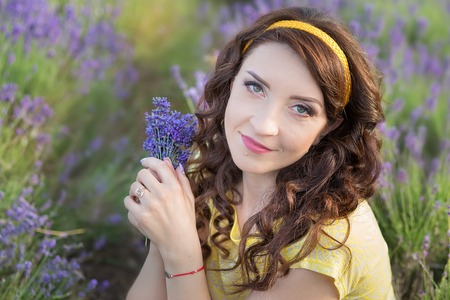 Young mother with young daughter smiling on the field of lavender .Daughter sitting on mother hands.Girl in colorful dress and mother in dark blue dress
