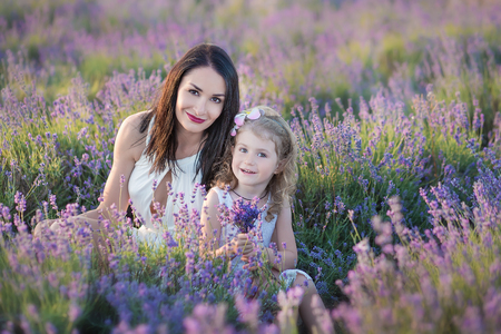Young beautiful lady mother with lovely daughter walking on the lavender field on a weekend day in wonderful dresses and hats