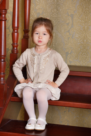 Young brunette dolly lady girl stylish dressed in white skirt midi petticoat and cardigan strap shoes smiling posing sitting in studio on wooden stairs ladder with pout lips and pink cheeks.