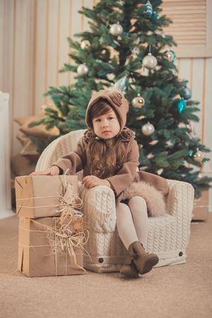Young brunette dolly lady girl stylish dressed cozy warm winter gray jacket with fur posing sitting standing in studio close to Christmas New Year tree and presents. Stock Photo