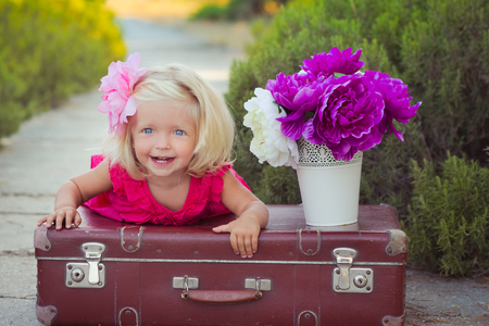 Amazing deep blue eyes baby girl child stylish dressed colourful pink dress with shining blond hairs and white sandals posing sit for camera summer central park forest meadow with flowers and trunk. Stock Photo