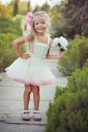 Amazing deep blue eyes baby girl child stylish dressed colourful pink dress with shining blond hairs and white sandals posing sit for camera summer central park forest meadow with flowers and trunk. Reklamní fotografie