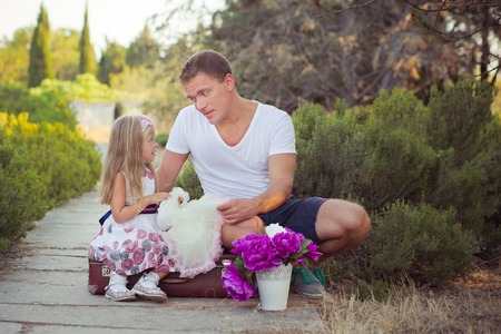 Family scene handsome young dad father posing playing with his baby daughter in central park forest summer meadow Happy life time vacation travel.