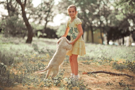 Retriever pup Lovely scene cute young teen girl enjoying posing summer time vacation with best friend dog ivory white labrador puppy.Happy airily careless childhood life world of dreams with puppies. Stock Photo