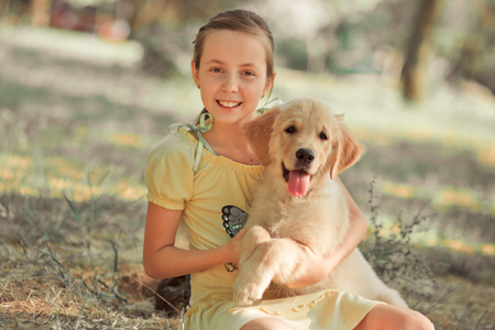 Retriever pup Lovely scene cute young teen girl enjoying posing summer time vacation with best friend dog ivory white labrador puppy.Happy airily careless childhood life world of dreams with puppies. Reklamní fotografie