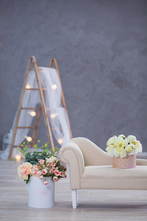 Studio interier decoration with flowers in light warm colors and casual vintage furniture. Archivio Fotografico