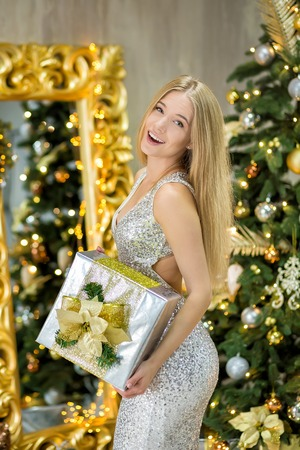 fashion interior photo of beautiful gorgeous woman with blond hair in luxurious dress posing in room with Christmas tree and decorations Imagens