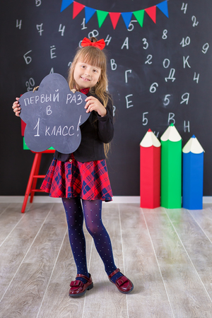 Cute school girl posing in studio shoot in school uniform dress and jacket on background of letters . Teen holding books .Girl holding blackboard on which written - first time in first class.