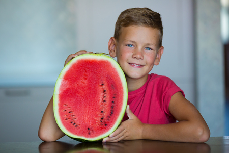 Cute kid enjoy summer juicy berry fruit watermelon Handsome blue eyes Boy wearing red t-shirt with slice of watermelon isolated on home studio kitchen