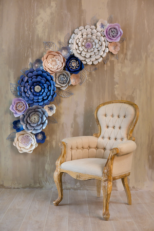 Cozy retro stylish home with decor inspired by designers and florist soul with royal colors. old fashion furniture chair in studio shoot with cosy paper flowers on background brown wall.