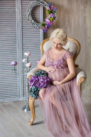 Pregnancy, motherhood and happy future mother concept - pregnant woman in airy violet dress with bouquet flowers against colorful wall posing with silver candelabrum.