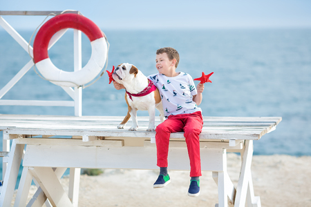 Handsome boy teen happyly spending time together with his friend bulldog on sea side Kid dog holding playing two sea stars close to life buoy float wearing red pants trousers slippers and t-shirt. 版權商用圖片