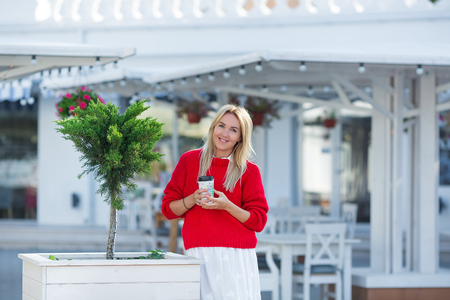Close-up portrait of magnificent caucasian girl lady wearing red sweater and white skirt. Lovable long-haired blonde woman enjoying life and having fun at resort cafe Фото со стока