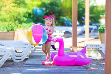 Baby girl on beach with pink flamingo dressed in stylish swimming wear posing on wooden floor. Scene on vacation on sea side of a cute lady smiling and enjoy life time childhood infancy 스톡 콘텐츠
