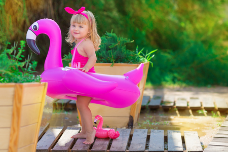Baby girl on beach with pink flamingo dressed in stylish swimming wear posing on wooden floor. Scene on vacation on sea side of a cute lady smiling and enjoy life time childhood infancy Stok Fotoğraf