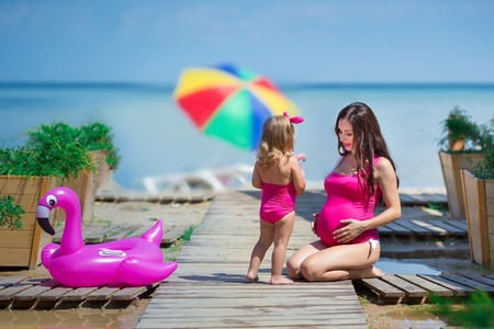 Pregnant woman on beach healthy vacation posing with cute baby daughter wearing pink stylish swimming wear. Family love scene of beautiful lady and funny child girl