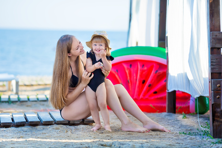 Happy family lifestyle. Relaxing and enjoying life. Bright colors. Top view Young mother with cute daughter Summer travel, water sport outdoor activities, posing on tropical beach holiday.