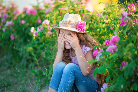 Cute brunette child blue eyes girl is holding flowers standing in pink rose field. Wearing stylish dress and hat, enjoy summer time days childhood.