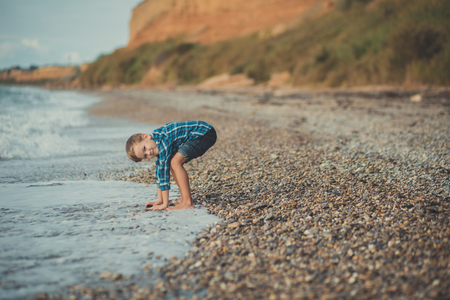 Cute boy kid child wearing stylish shirt and blue jeans barefoot posing running on stone beach with gorgeous ocean sea landscape sand cliff cape. Фото со стока