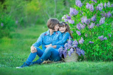 Cute adorable beautifull mother lady mom woman with brunette girl daughter in meadow of lilac purple bush.People in jeans wear 写真素材