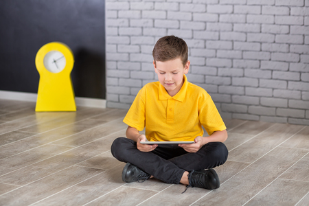 Cute handsome school boy in yellow t-shirt tie and stylish boots casuals standing cloase to black board with numbers and holding tablet and smiling.