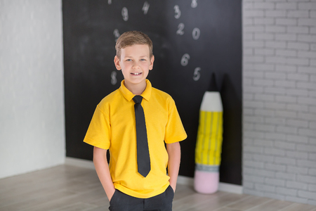 Cute handsome school boy in yellow t-shirt tie and stylish boots casuals standing cloase to black board with numbers and holding huge big soft toy pencil and smiling.