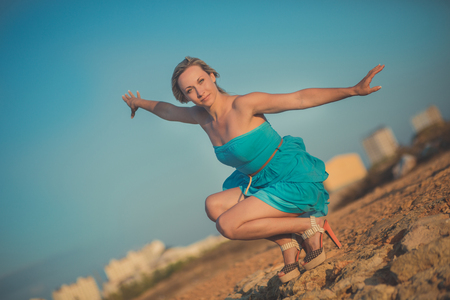 Seductive blond lady woman with sexy legs shoulders and arms wearing light blue open dress posing enjoying vacation time on sea side ocean beach alone.