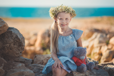Blond girl pretty with blue eyes wearing light dress and wild flowers wreath on top head posing in ancient city stones close to seaside beach with teddy bear.