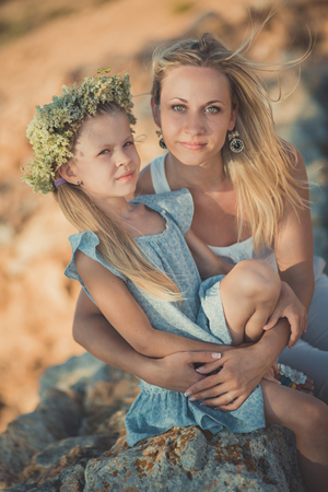 happy family having fun outdoors. Portrait of adorable mother and cute pretty daughter enjoying time together in ancient city stones on sea side beach wearing light stylish clothes.