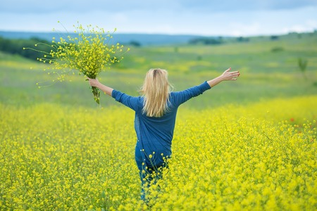 Genuine cute lady woman in meadow of yellow flowers sniffing flower bouquet. Attractive beautiful young girl enjoying the warm summer sun in a wide green and yellow meadow Stylish dressed