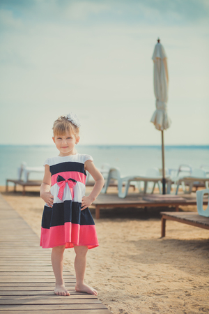 Young cute baby girl enjoying childhood summer time on sandy beach posing on wooden pier bridge wearing casual stylish dress.